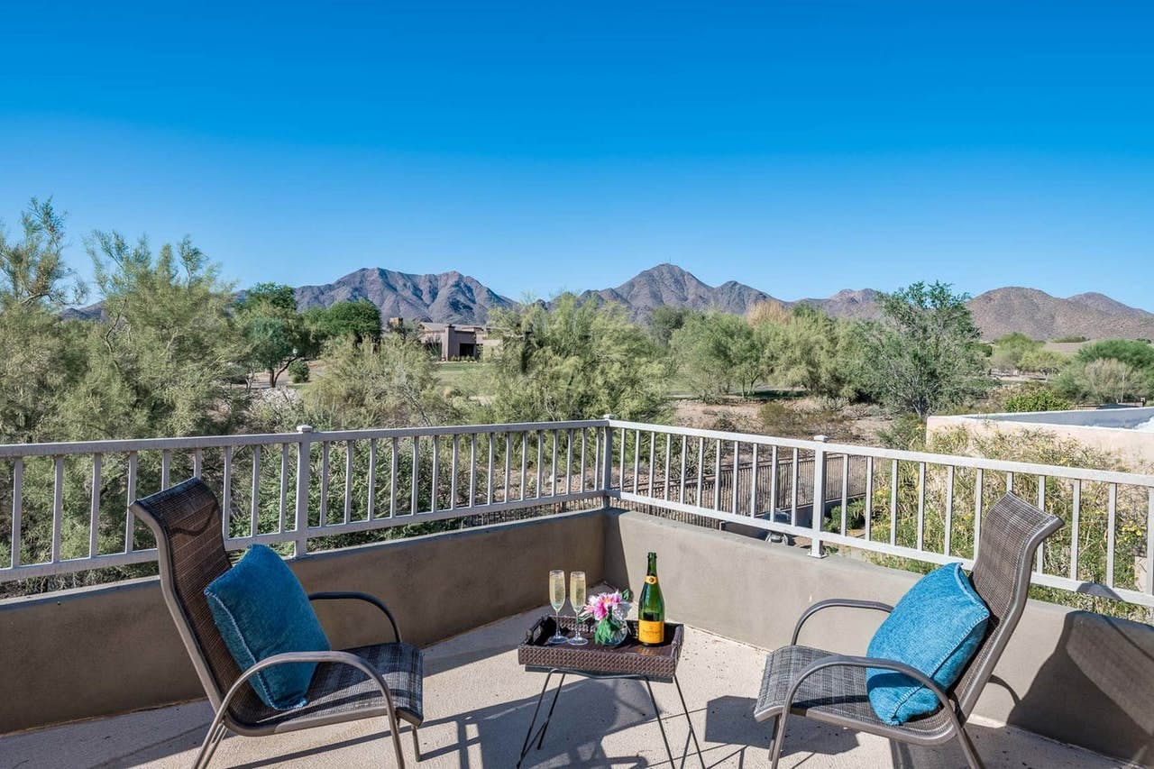 a bottle of champagne on a table with views of the arizona desert in the backdrop