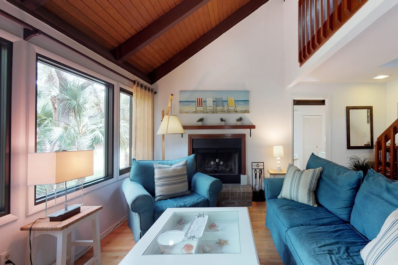 a living room with blue couches and a clear coffee table with sea ornaments underneath