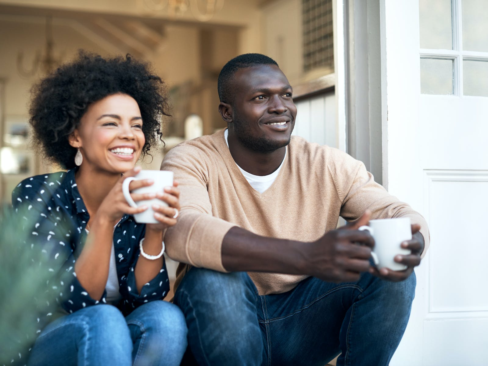 A couple enjoying coffee on the front porch of their vacation rental