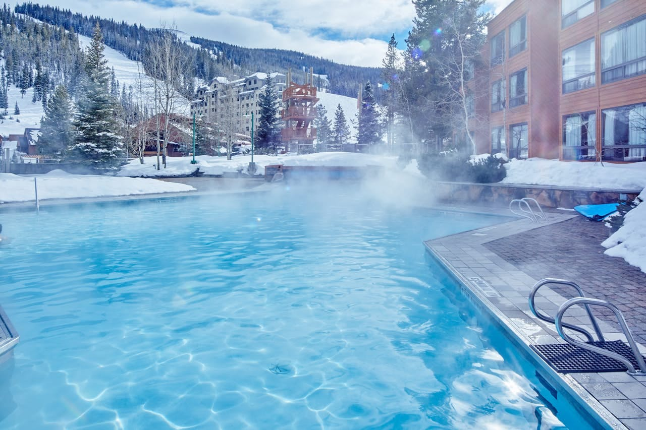 Big Sky condo with heated pool surrounded by snow