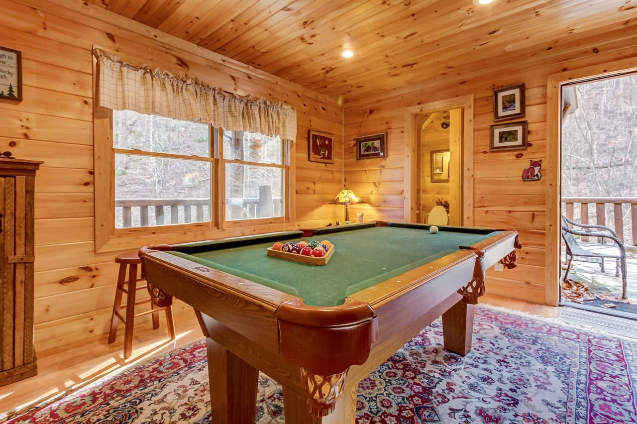 a pool table inside of a smoky mountain cabin