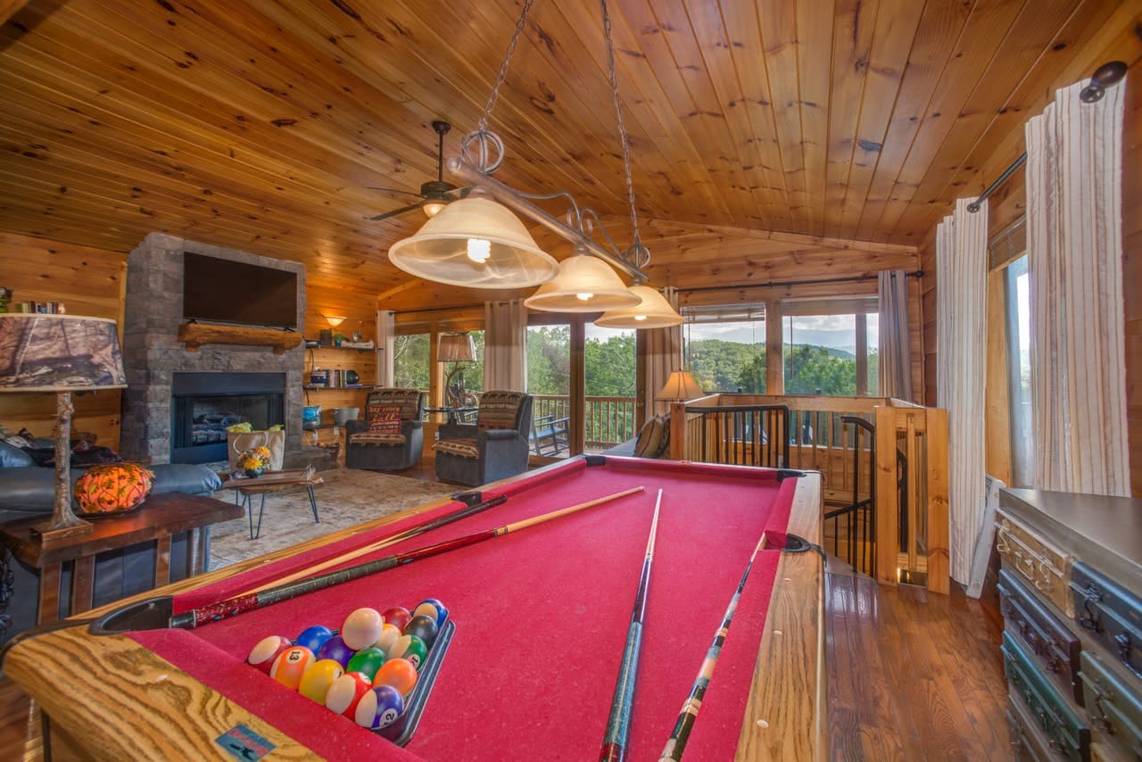 a red velvet pool table set up inside of a cabin's living room