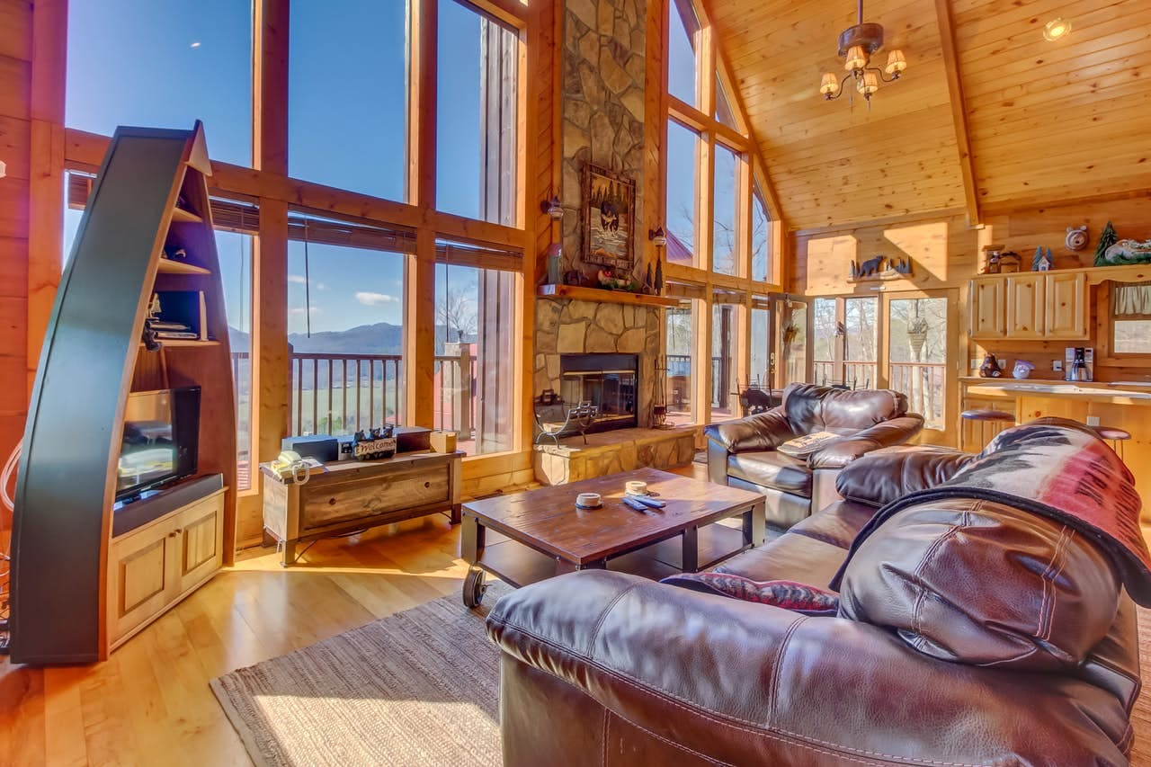 a cabin's living room that overlooks the smoky mountains on a sunny day