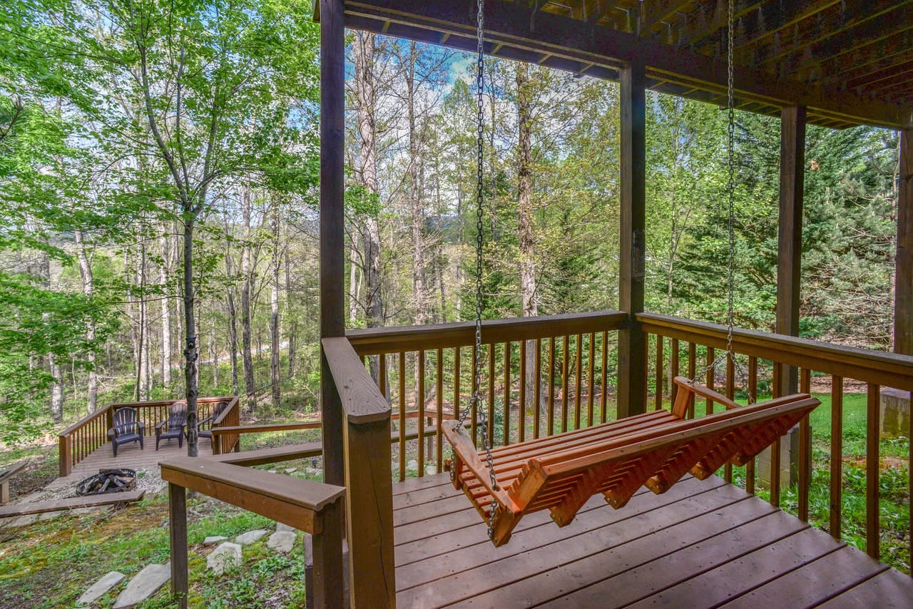 a porch swing overlooking a backyard and the forest