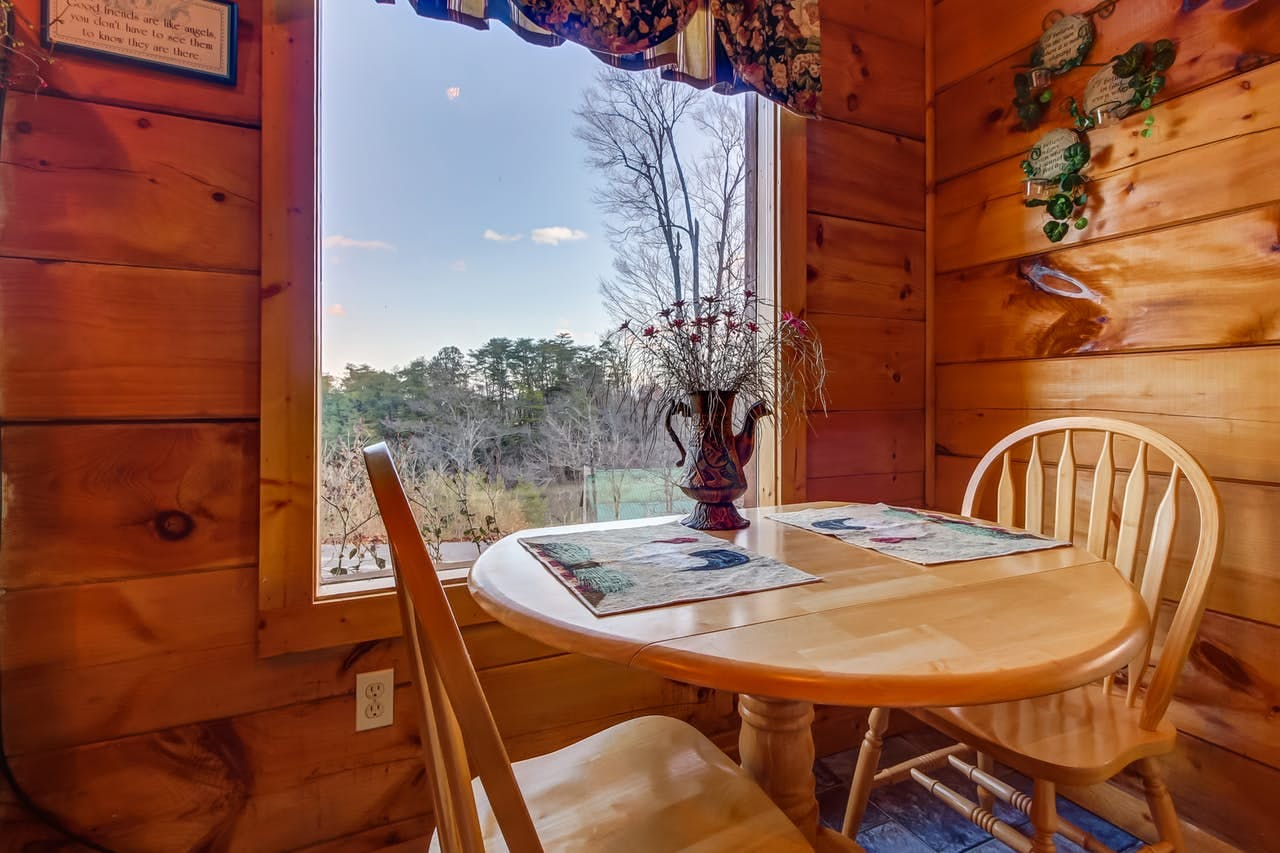 a two person dining room table that overlooks a backyard in the smoky mountains