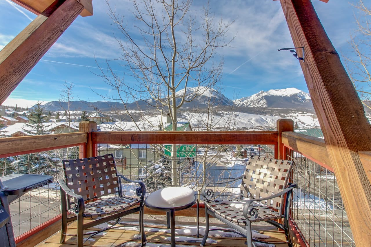 Two chairs on the deck of a Dillon, CO vacation home, with views of the mountains in the background