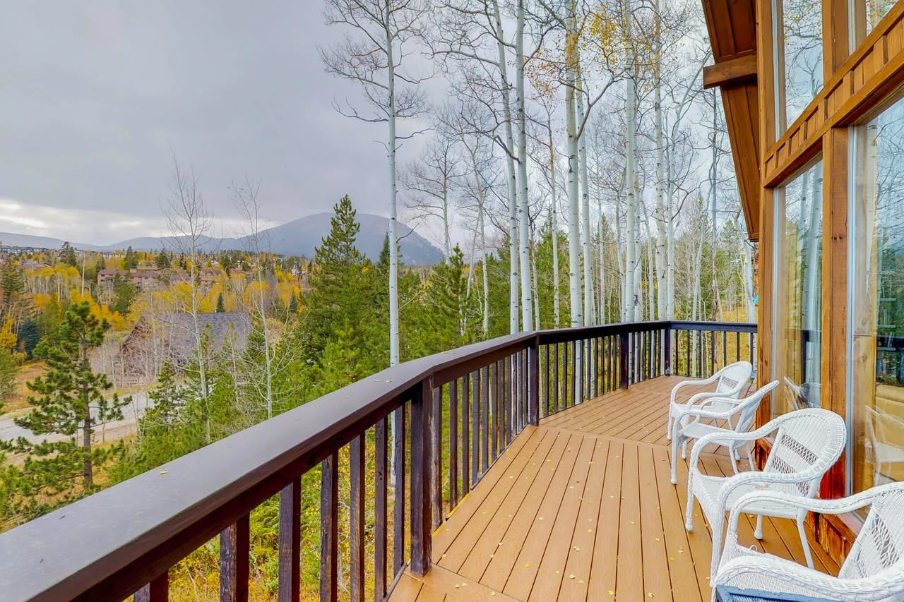 the deck of a Silverthorne, CO vacation home that overlooks the forest as the leaves change colors