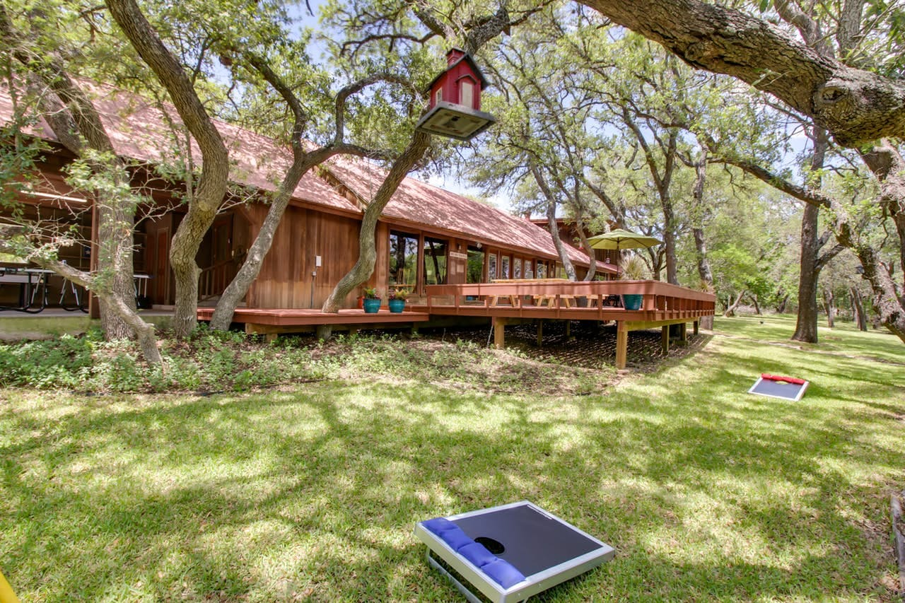 ranch-style Redwood home with large porch and backyard with cornhole