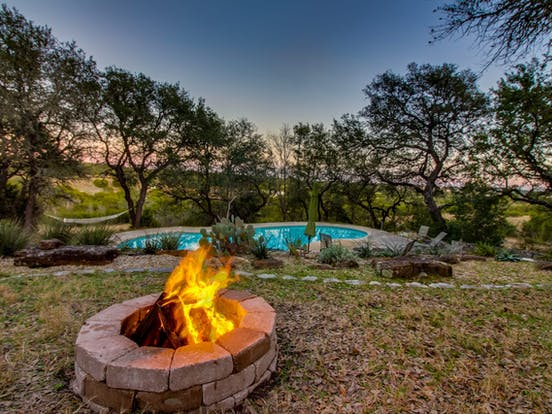 Gorgeous backyard of Dripping Springs vacation rental with firepit and pool