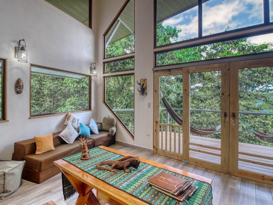 Living area and balcony of a vacation treehouse rental in Costa Rica
