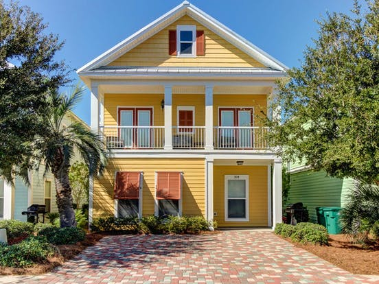 Yellow beach house rental with orange shutters in Destin, FL