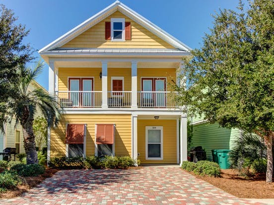 Yellow beach house with orange shutters located in Destin, FL