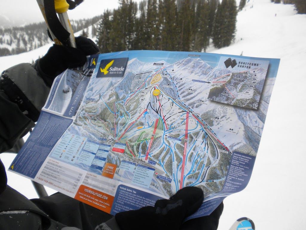 a skier looking at a map of Solitude as they ride the ski lift