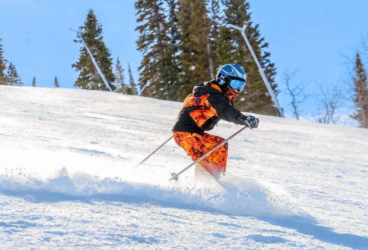 a skier in park city going down a run on a sunny spring day