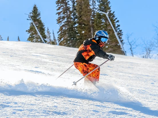 a skier wearing an orange outfit going down the slopes at Park City