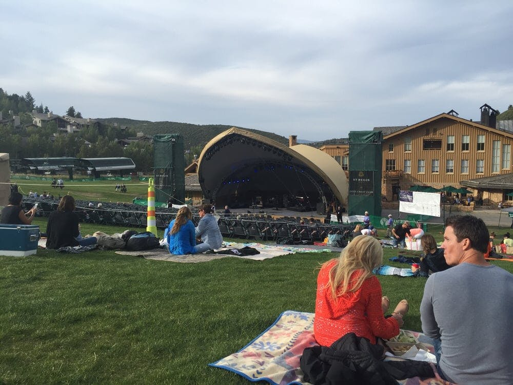 people having a picnic and enjoying a sunny day at Snow Park Outdoor Amphitheater