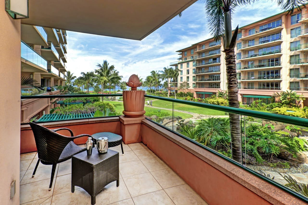 Open air balcony with ocean and pool views from a Honua Kai suite