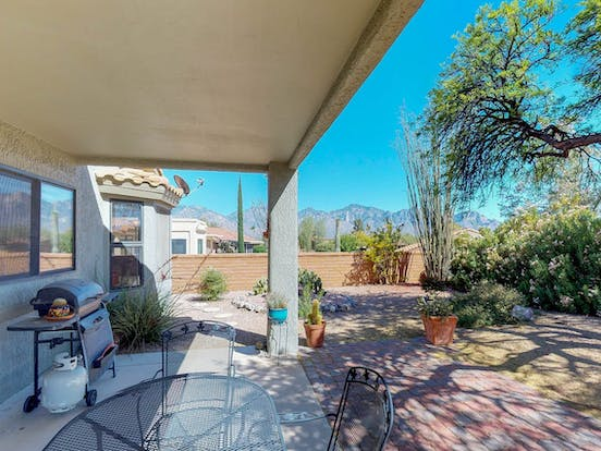 Backyard features patio seating, gas grill and beautiful landscaping in this Arizona vacation home