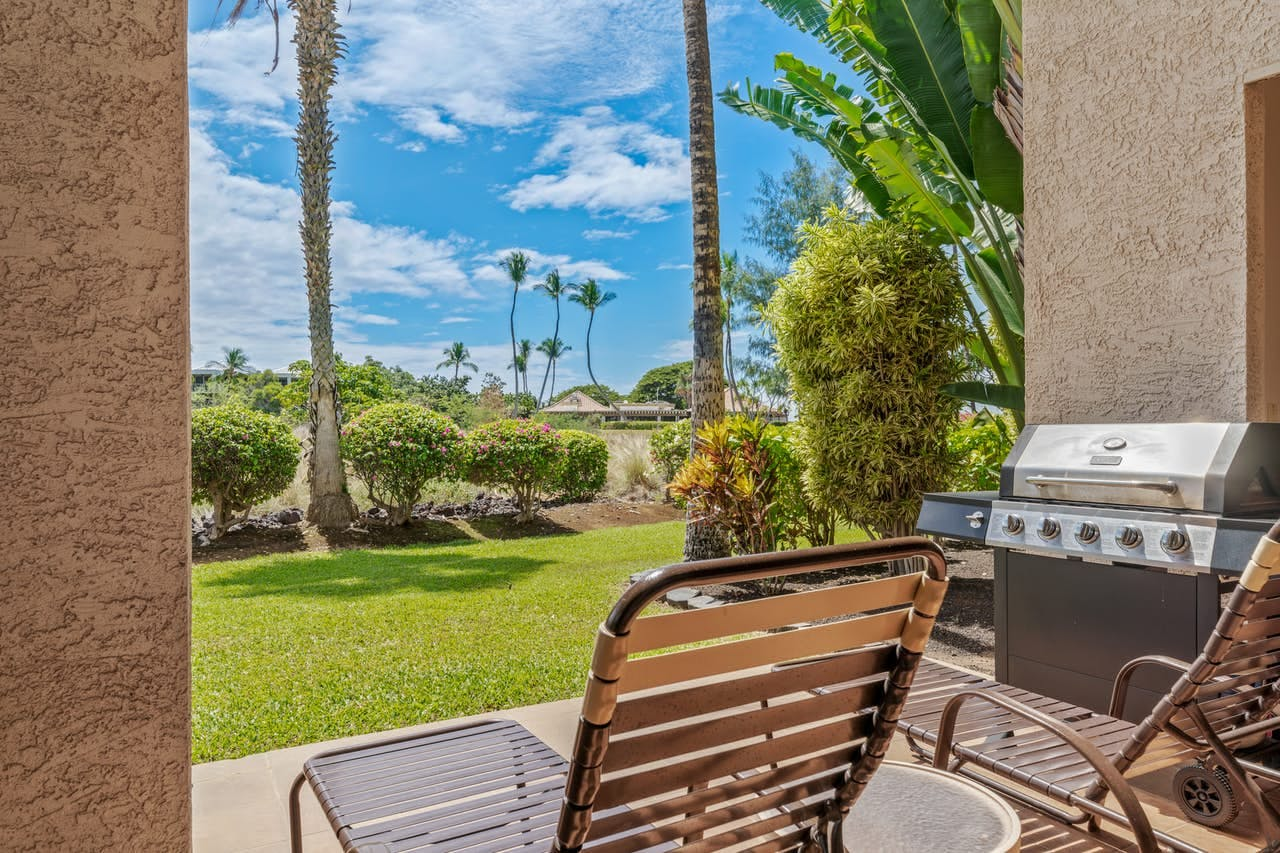 Patio with lounge chair and grill overlooking green manicured lawns at Shores at Waikoloa resort