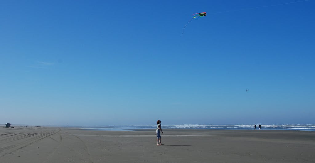 a girl flying a kite at Ocean Shores on a sunny day