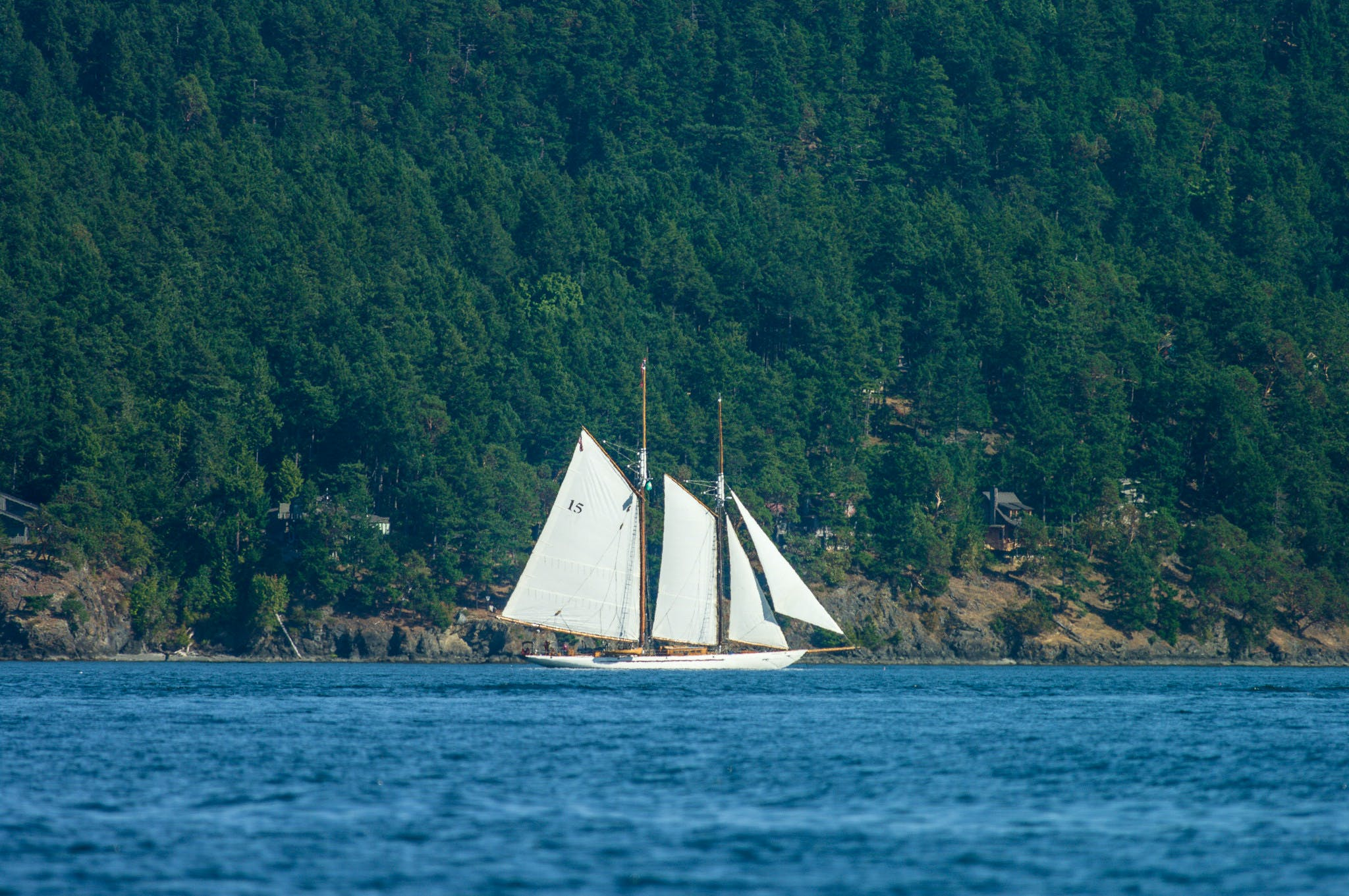 a large sailboat cruising through the water in the san juans