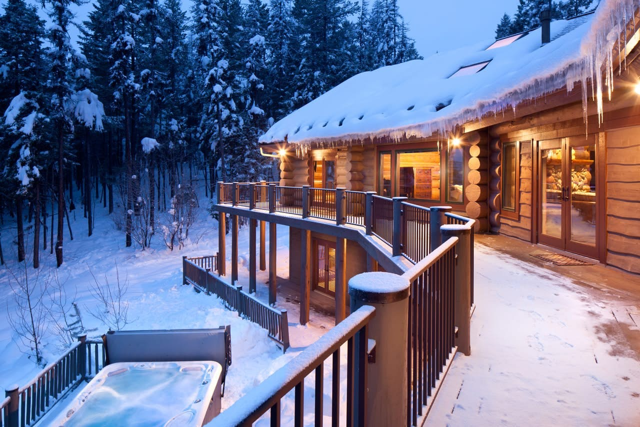 outside a Whitefish cabin in the wintertime, with the warm hot tub in the snow