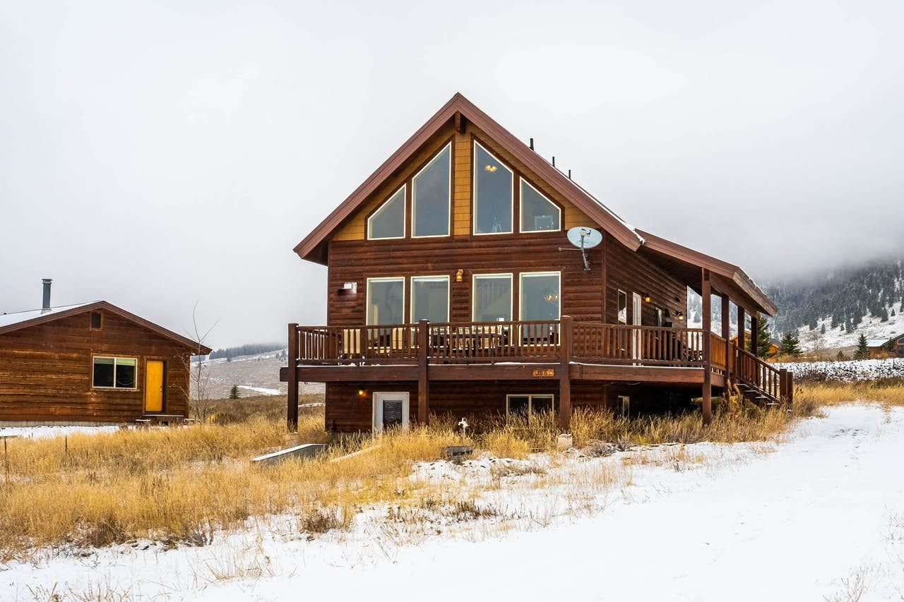 Island Park, ID vacation home with large windows and wraparound deck