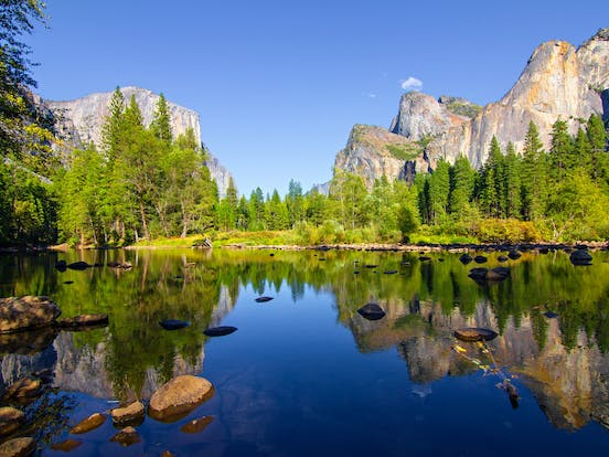View of Yosemite waters and rock formations surrounded by woods