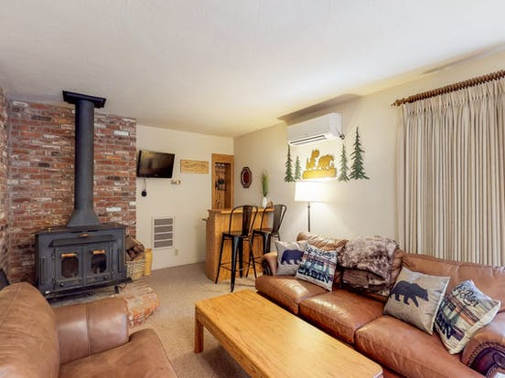 living room of Groveland cabin rental with two leather couches, fireplace and corner bar
