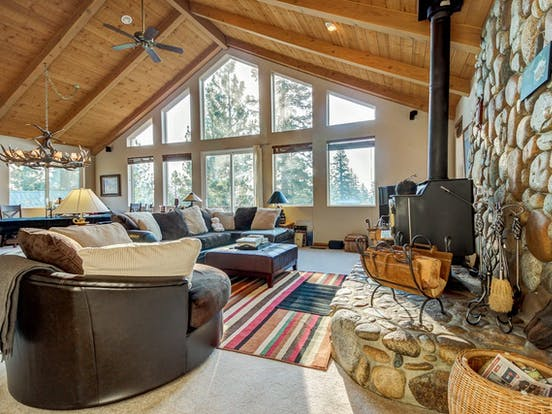 mountain lodge vacation rental with ample seating, a large stone fireplace and floor-to-ceiling windows